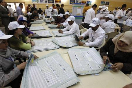 Officials count parliamentary election ballots at the tally centre in Baghdad March 10, 2010. REUTERS/Thaier al-Sudani/Files