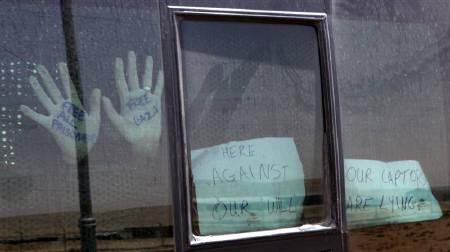 A Pro-Palestinian activist, arrested aboard a Gaza-bound ship, places his hands against the window of a bus as it leaves Ella prison in the southern Israeli city of Beersheba June 2, 2010. REUTERS/Alberto Denkberg