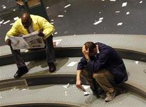<p>A trader holds his head as another reads a paper after markets closed in the natural gas feature pit of the New York Mercantile Exchange in New York June 6, 2008. REUTERS/Joshua Lott</p>