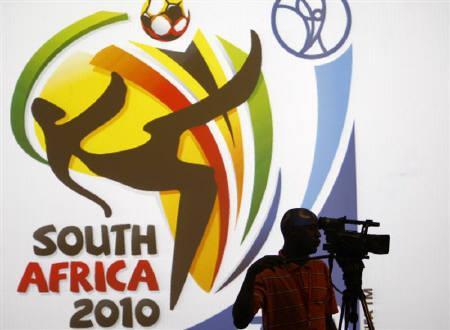 6月2日、サッカーW杯南アフリカ大会がを中継するテレビ局は高額な放映権料を支払っているが、利益を出すのは難しいとの見方もある。写真は2月、南アフリカ大会のポスターの前に立つカメラマン(2010年 ロイター/Siphiwe Sibeko)