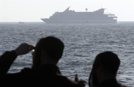 Ultra-orthodox Jews watch as the Mavi Marmara, a Gaza-bound ship that was raided by Israeli marines, is escorted to Ashdod port by an Israeli naval vessel (not seen) May 31, 2010. REUTERS/Amir Cohen/Files