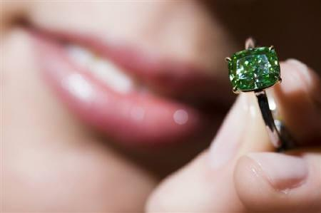 A model displays a rare a cushion modified brilliant-cut fancy vivid green diamond weighing 2.52 carats during an auction preview at Sotheby's in Geneva November 11, 2009. REUTERS/Valentin Flauraud/Files