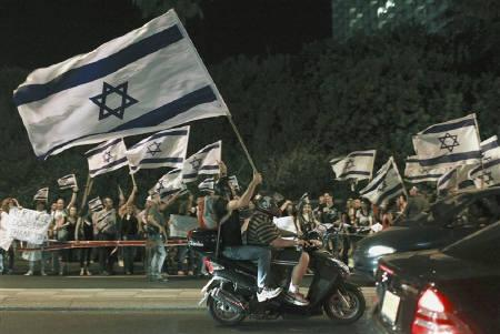 Protesters drive by as they hold up Israeli national flags during a pro-Israel rally in Tel Aviv June 3, 2010. Israel is unlikely to heed calls to lift the blockade of the Gaza Strip but its bloody seizure of a Turkish aid ship has caused international anger and American dismay that is forcing it to seek conciliatory moves. REUTERS/Nir Elias