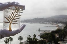 """<p>Представитель компании Chopard демонстрирует награду """"Золотую пальмовую ветвь"""" в Каннах 11 мая 2010 года. Сингапур станет азиатскими Каннами в июне 2011 года, надеются организаторы нового кинофестиваля """"ScreenSingapore"""". REUTERS/Christian Hartmann</p>"""