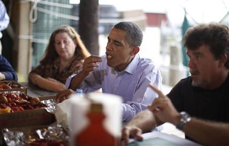 U.S. President Barack Obama eats a locally-caught shrimp with David Camardelles (R) and convenience store owner Patti Gaspard during a meeting with locals in Grand Isle, Louisiana, June 4, 2010. REUTERS/Jason Reed