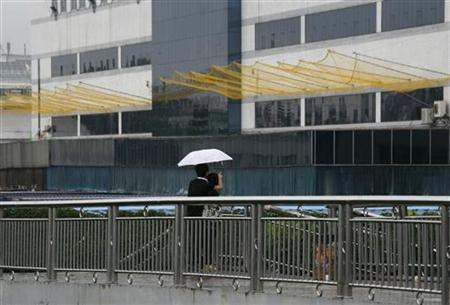 A couple stand on a footbridge in front of nets, newly installed to prevent workers from jumping to their deaths, outside one of Foxconn's factory buildings in the township of Longhua, in southern Guangdong province June 2, 2010. REUTERS/Bobby Yip