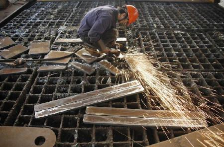 A labourer welds steel frames at a steel factory in Huaibei, Anhui province June 2, 2010. REUTERS/China Daily