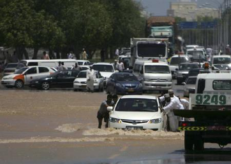 A car is pushed through floodwaters brought about by Cyclone Phet in Muscat June 5, 2010. Damages from Cyclone Phet, which pummelled the Omani coastline last week and killed 21 people, could cost the Gulf Arab state over 300 million rials ($780 million), a government official said on Monday. REUTERS/Herbert Fernandes