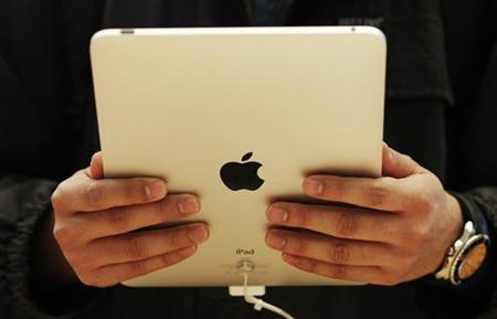 A customer holds the new iPad tablet computer at its UK launch at an Apple store in central London May 28, 2010. REUTERS/Luke MacGregor