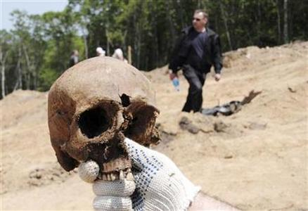 A researcher holds a human skull at the site where people were shot by the Soviet authorities under Josef Stalin outside the far eastern city of Vladivostok June 7, 2010. REUTERS/Yuri Maltsev