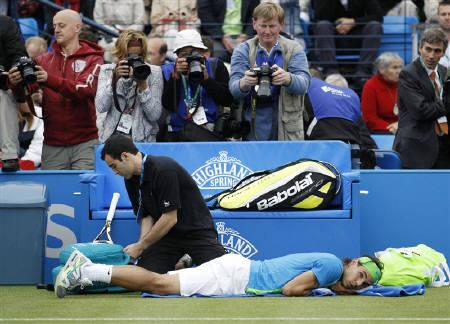 Photographers take pictures as Rafael Nadal of Spain is assisted by a medic during his tennis match against Denis Istomin of Uzbekistan at the Queen's Club Championships in west London June 10, 2010. REUTERS/Suzanne Plunkett