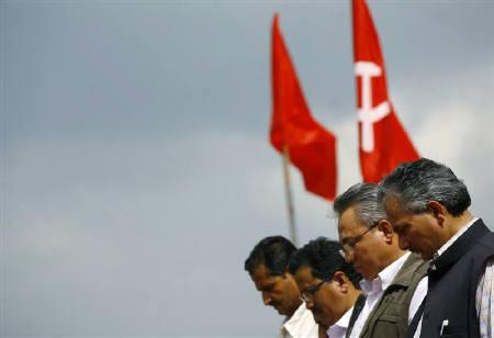 Maoist leaders stand in front of their party flags with their heads bowed during a minute of silence in memory of their slain comrades before the start of a ceremony in Kathmandu May 29, 2010. REUTERS/Deepa Shrestha/Files