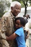 <p>O ex-presidente sul-africano Nelson Mandela abraça sua bisneta Zenani Mandela en Diepkloof, Soweto, nesta foto arquivo de 2008. Mandela não comparecerá à partida de abertura da Copa do Mundo a morte da bisneta em um acidente de carro. 07/12/2008 REUTERS/Fundação Nelson Mandela/Divlugação</p>