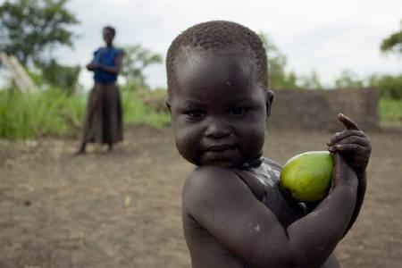 An internally displaced child plays with a mango fruit in Pabbo refugee camp in northern Uganda, April 27, 2007. What started as an ambitious attempt to establish, once and for all, a permanent international war crimes tribunal is still trying to gain credibility seven years after its birth. REUTERS/James Akena/Files