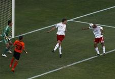 <p>Simon Poulsen, da Dinamarca, cabeceia e marca gol contra na partida contra a Holanda, que venceu por 2 x 0, na estreias das seleções na Copa da África do Sul. REUTERS/David Gray</p>