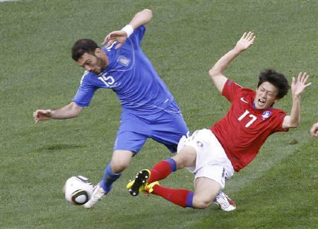 Greece's Vassilis Torosidis (L) fights for the ball against South Korea's Lee Chung-yong during the 2010 World Cup Group B soccer match at Nelson Mandela Bay stadium in Port Elizabeth June 12, 2010. REUTERS/Oleg Popov