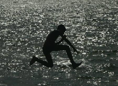 A boy jumps into a lake to beat the heat on a hot day in Bhopal April 30, 2010. REUTERS/Raj Patida/Files
