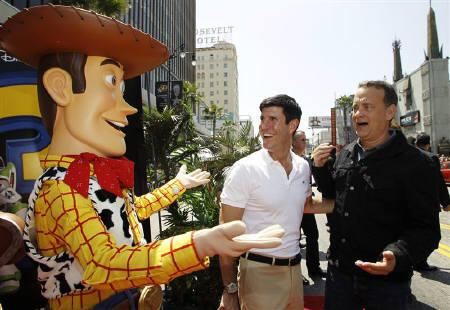 The Walt Disney Studios Chairman Rich Ross and actor Tom Hanks (R) greet the character Woody, whose voice Hanks plays in Disney Pixar's ''Toy Story 3'', at the world premiere of the film at the El Capitan Theatre in Hollywood, California June 13, 2010. REUTERS/Danny Moloshok
