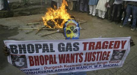 A child wearing a mask holds a banner in front of a burring mock pyre during a protest organised by Sadhbavana Adhikar Manch, a Non-Governmental Organisation, against the Bhopal gas disaster verdict in Bhopal June 15, 2010. REUTERS/Raj Patidar/Files
