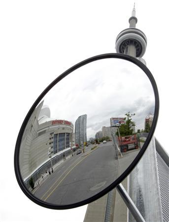 The Rogers Centre, home of the Toronto Blue Jays, is reflected in a mirror attached to security fence for the upcoming G20 Summit near the CN Tower in Toronto June 14, 2010. REUTERS/Mike Cassese