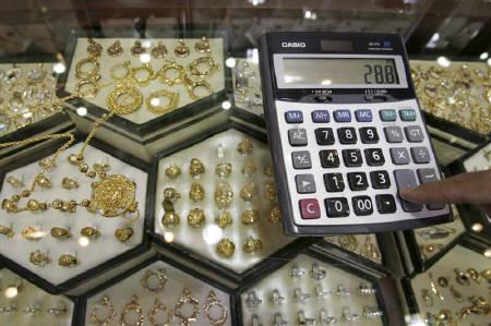A Jordanian goldsmith calculates the price of a gold coin for customers at his shop in Amman June 9, 2010. REUTERS/Muhammad Hamed/Files