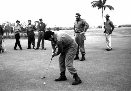 Ernesto ''Che'' Guevara plays golf as Fidel Castro stands behind him at Colina Villareal in Havana in this undated file picture. REUTERS/Prensa Latina/Files