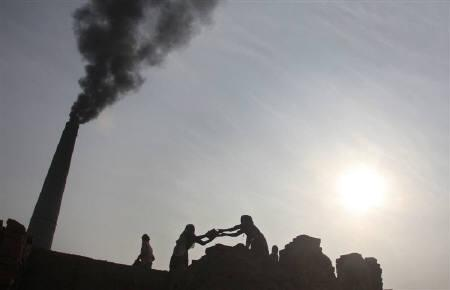 Labourers work as smokes rise from a chimney of a brick factory at Togga village on the outskirts of Chandigarh December 6, 2009. REUTERS/Ajay Verma/Files