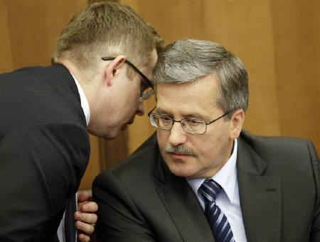 Bronislaw Komorowski (R), speaker of the parliament and presidential candidate from the Civil Platform Party (PO), speaks to his advisor during a trial at a court house in Warsaw June 22, 2010. Poland's centrist presidential candidate Komorowski faces a tight run-off vote against his right-wing rival Kaczynski on July 4 after beating him by only a
