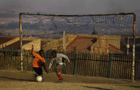 Children play a game of soccer just ahead of the FIFA 2010 World Cup soccer match between South Africa and France at Soweto in Johannesburg, June 22, 2010. REUTERS/Kai Pfaffenbach