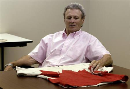 Canadian hockey legend Paul Henderson touches the Team Canada jersey he wore when he scored the winning goal during the 1972 Summit Series against the Soviet Union at his office in Mississauga June 7, 2010. A Canadian company paid more than $1 million for the white and red jersey. REUTERS/Mike Cassese