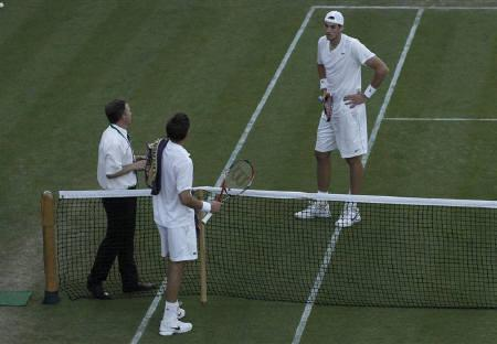 France's Nicolas Mahut (C) and John Isner of the U.S. talk to tournament official, Soeren Friemel, who suspended play due to darkness in their match at 59-59 in the fifth set at the 2010 Wimbledon tennis championships in London, June 23, 2010. REUTERS/Suzanne Plunkett