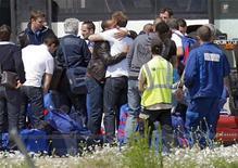 <p>Thierry Henry (6o à esq) abraça colega de equipe após chegarem ao aeroporto de Le Bourget próximo a Paris. A seleção francesa retornou sob forte proteção da polícia nesta quinta-feira depois de uma humilhante desclassificação na primeira fase da Copa do Mundo. 24/06/2010 REUTERS/Gonzalo Fuentes</p>