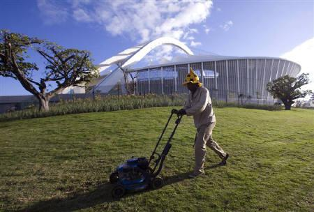 A gardener mows the grass at the Moses Mabhida Stadium in Durban, June 3, 2010. REUTERS/Rogan Ward/Files