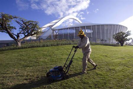A gardener mows the grass at the Moses Mabhida Stadium in Durban, June 3, 2010. REUTERS/Rogan Ward/Files