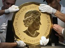 <p>Experts of an Austrian art forwarding company remove the world's largest gold coin, a 2007 Canadian $ 1,000,000 Maple Leaf with a weight of 100 kilos and a diameter of 53 cm from Dorotheum auction house after the auction in Vienna June 25, 2010. REUTERS/Heinz-Peter Bader</p>