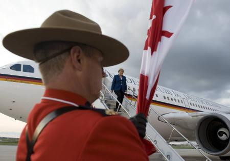 A Royal Canadian Mounted Police officer holds Canada's national flag as German Chancellor Angela Merkel arrives at Pearson International Airport ahead of the G8 and G20 Summits in Toronto June 24, 2010. Merkel arrived on a German government Airbus A310 aircraft.  REUTERS/BPA/Guido Bergmann/Handout