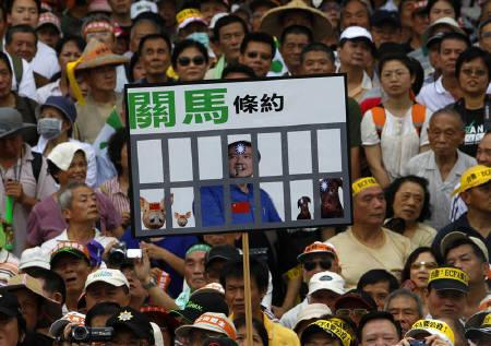 People carry a placard during a protest against the economic cooperation framework agreement (ECFA) to be signed between China and Taiwan, in Taipei June 26, 2010. REUTERS/Nicky Loh