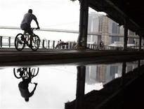 <p>A man rides his bike under the FDR East River Drive in New York July 24, 2008. The National Weather Service issued a Flash Flood Watch for New York City through Thursday evening. REUTERS/Shannon Stapleton</p>