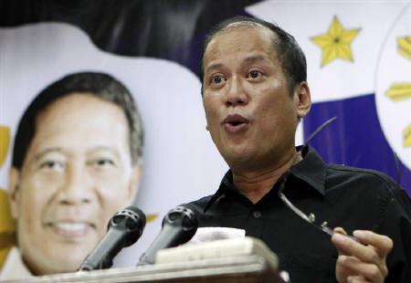 Philippine President-elect Benigno ''Noynoy'' Aquino III speaks beside a poster of Vice-President elect Jejomar Binay during a news conference after announcing members of his cabinet in Quezon City, Metro Manila June 29, 2010. REUTERS/Erik de Castro