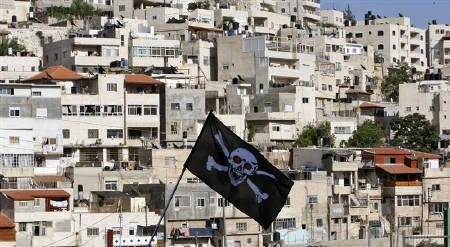 Left wing activists hold the skull and bones flag during a protest against Jewish settlement activity in the Silwan neighbourhood, outside the old city in Jerusalem, June 25, 2010. REUTERS/Baz Ratner/Files