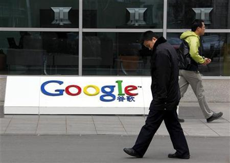 A security guard (L) and an employee walk past Google's logo outside Google China headquarters building in Beijing March 24, 2010. REUTERS/David Gray