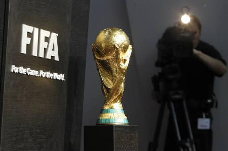 A cameraman films next to a replica of the World Cup trophy during a press conference in Zurich March 5, 2010. Thieves stole seven replicas of the golden World Cup trophy from FIFA's headquarters in South Africa, police and soccer officials said on Tuesday. REUTERS/Christian Hartmann/Files