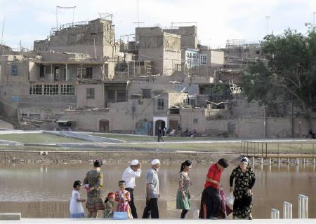 Residents walk in front of a section of a historic neighborhood which is being rebuilt in Kashgar, in China's frontier Xinjiang Autonomous Region June 13, 2010. REUTERS/Lucy Hornby/Files