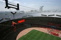 """<p>Adili Wuxor, known as """"Prince of the Tightrope"""", is lowered while holding the Chinese national flag at the """"Bird's Nest"""" Olympic stadium in Beijing July 2, 2010. REUTERS/Bobby Yip</p>"""