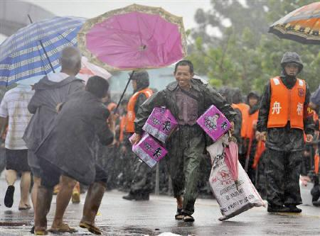 A resident smiles as he carries boxes of instant noodles provided by People's Liberation Army (PLA) under heavy rain in Fuzhou, Jiangxi province June 24, 2010. China's urban population is to surpass its rural population for the first time by 2015, Xinhua news agency reported. REUTERS/Stringer/Files