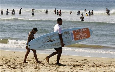 A surfing instructor and his student head towards the Indian Ocean surf on Durban beach June 20, 2010. REUTERS/Paul Hanna