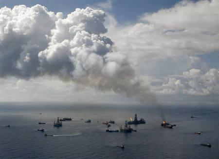 Smoke rises from the BP oil spill site, as natural gas is burned off, while the drilling of two relief wells continue in the Gulf of Mexico, July 4, 2010.    REUTERS/Lyle W. Ratliff