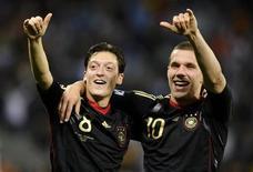 <p>Mesut Ozil e Lukas Podolski (dir) da seleção alemã comemoram após vitória das quartas de final da Copa contra a Argentina. Noventa por cento dos alemães com TV assistiram à vitória arrasadora de sua seleção por 4 x 0 no sábado, disse a Fifa nesta terça-feira. 03/07/2010 REUTERS/Dylan Martinez</p>