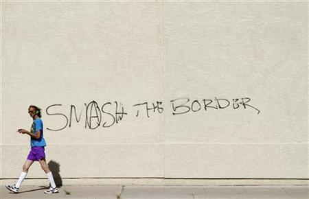 A man walks past graffiti on a building reading ''Smash The Border'' in Phoenix, April 29, 2010. REUTERS/Joshua Lott