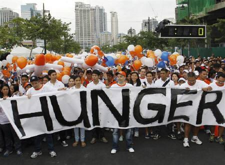 Participants tear a banner during the ''End Hunger: Walk the World'' in Manila June 6,  2010. Asian countries need to increase investment in food production by 50 percent to $120 billion a year to ensure they can afford to feed their large and growing populations, a United Nations' body said on Wednesday. REUTERS/Cheryl Ravelo/Files